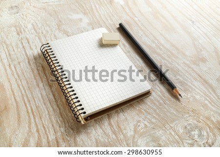 Sketchbook with a pencil and eraser on light wooden background with soft shadows. Template for graphic designers portfolios. Top view. - stock photo