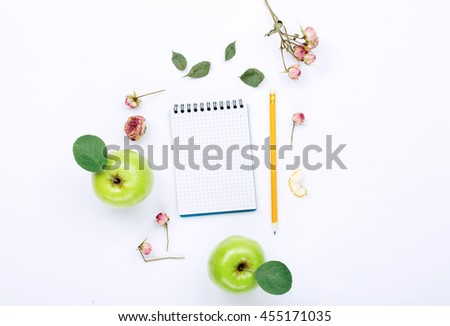 sketchbook with pencil, green apples with leaves and dry rose flowers. Flat lay, top view - stock photo