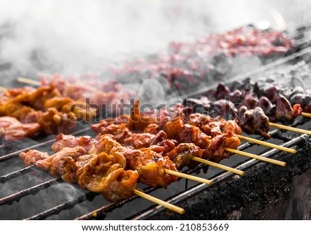 Skewer chicken pieces in a roasting on the grill and smoke  - stock photo