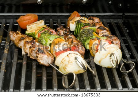 skewer of grilled vegetables and meat on a barbecue - shallow DOF