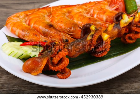 Skewer with octopus and prawn on banana leaves
