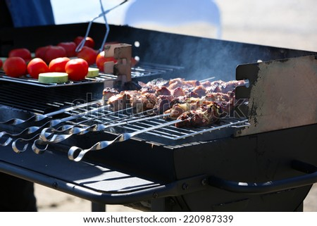 Skewers and vegetables on barbecue grill, close-up - stock photo