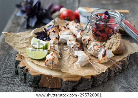 Skewers of chicken with salsa of basil, tomatoes and red onions served with yogurt sauce on a wooden background