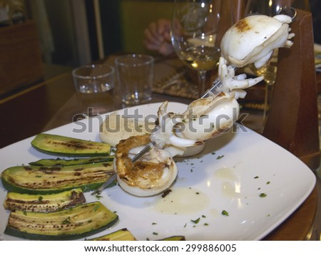 skewers of grilled cuttlefish with zucchini and white polenta, italian food