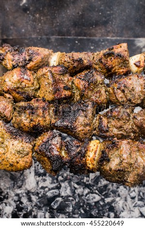 Skewers of lamb cooked on the grill. Wooden background. Top view. Close-up