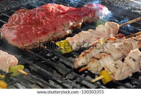 skewers of meat and beef fillet on the barbecue in the garden - stock photo