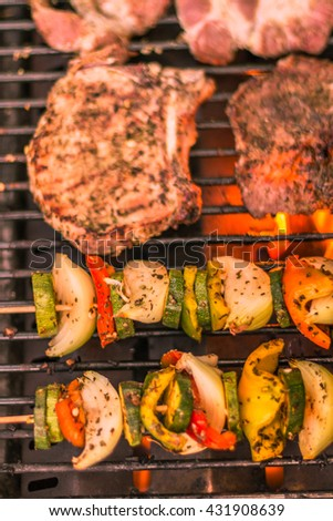 Skewers of meat and vegetables on the grill. Slices of meat with fresh herbs. - stock photo