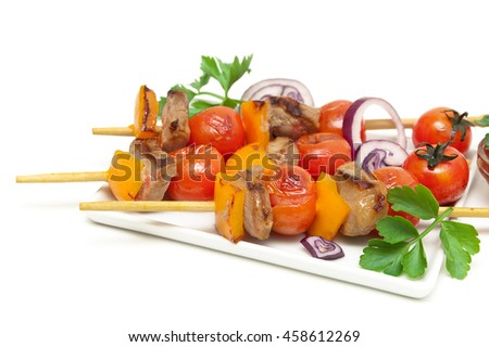 skewers of meat with vegetables on a plate close-up. white background - horizontal photo. - stock photo