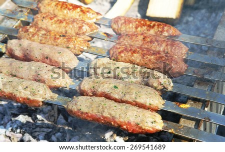 Skewers of minced meat on skewers outdoors - stock photo