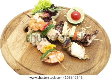 skewers of seafood on a wooden platter in a restaurant - stock photo