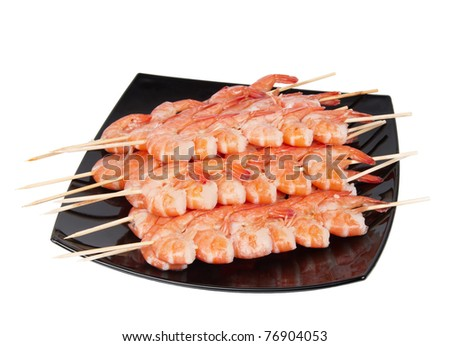 Skewers of shrimp on a black plate, isolated on a white background