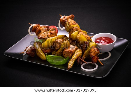 Skewers with meat, pepperoni peppers on black, top view - stock photo