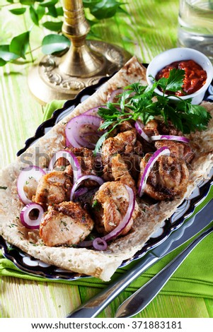 skewers with red onion on a thin pita bread in still life green wooden boards, the atmosphere of the restaurant, fork, tasty, appetizing, purple, green - stock photo