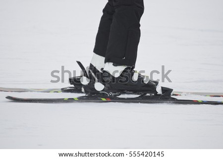 ski boots of an adult man as he descends the slope