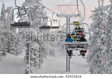 Ski chair lift  with skiers. Ski resort in Ruka, Finland - stock photo