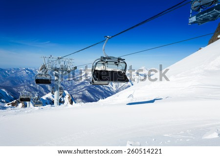Ski chairlift over mountains on winter resort  - stock photo