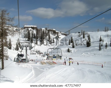 ski chairlift with skiers in Slovenia - stock photo