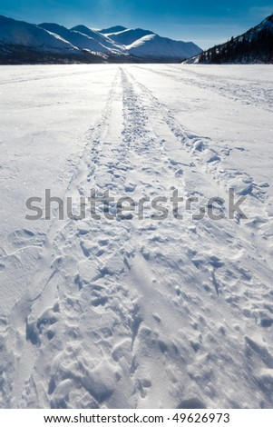 Ski-doo track on windblown snowy surface of frozen mountain lake in winter wonderland. - stock photo