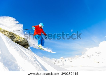 Ski freerider jumping from the rock in fresh powder snow in Alps.