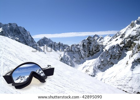 Ski goggles with reflection on slope of Caucasus Mountains. - stock photo
