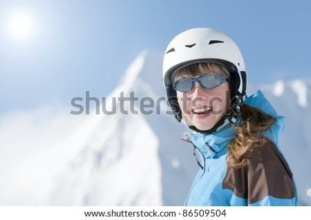 Ski holiday - portrait of teenage girl, snowy mountains in background - stock photo