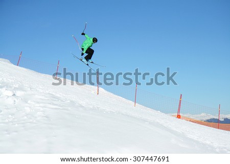 Ski jumper in a jump over the slope, blue sky in the background, Dolomites, Val di Fiemme, Italy