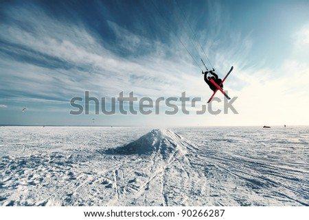 Ski kiting and jumping on a frozen lake - stock photo