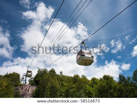 Ski lift against a cloudy blue sky. - stock photo