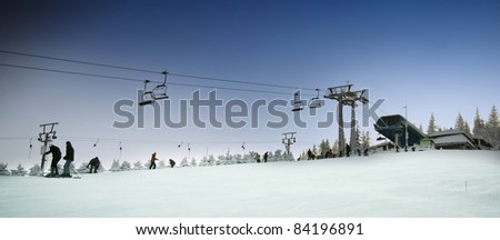 Ski lift chairs and ski slope - stock photo