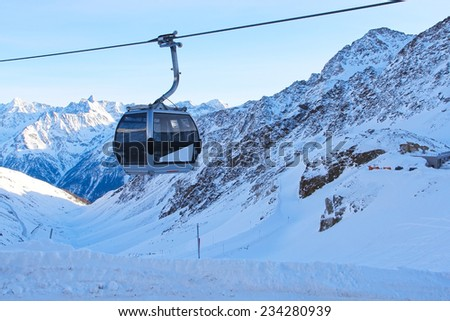 Ski lift chairs on bright winter day in Alp mountains - stock photo
