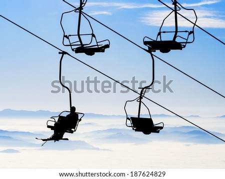 Ski lift chairs on bright winter day over the clouds - stock photo