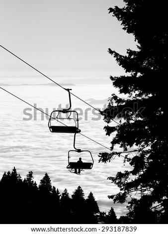 Ski lift chairs on bright winter day over the clouds, cableway funicular chair equipment, Garmisch Partenkirchen, Austria - stock photo