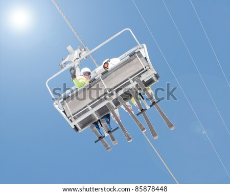 Ski lift - happy skiers on ski vacation - stock photo