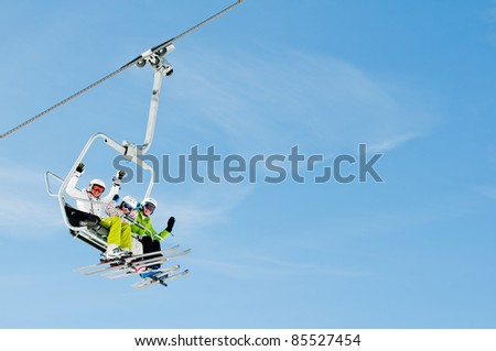 Ski lift - happy skiers on ski vacation (copy space) - stock photo
