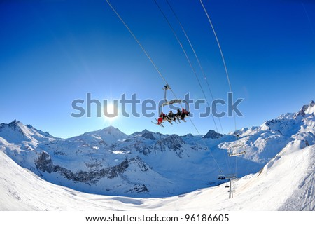 Ski lift - happy skiers use vertical transport  on ski vacation at sunny winter snow day - stock photo