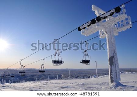 Ski lift in sunny but freezing weather - stock photo