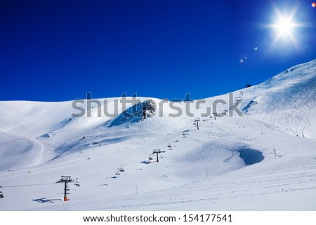 Ski lift lifting skiers on top of high mountain peak on the background - stock photo