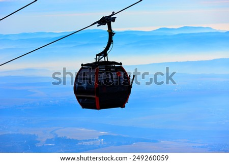 Ski lift over clouds on winter resort - stock photo