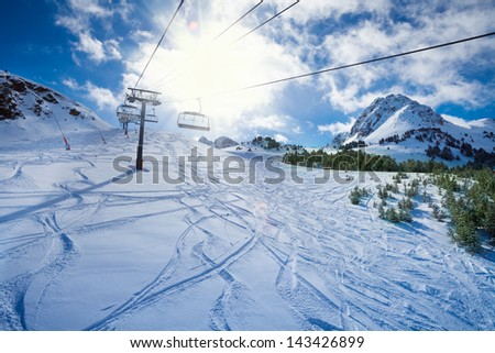 Ski lift with seats going over the mountain and paths from skies and snowboards - stock photo