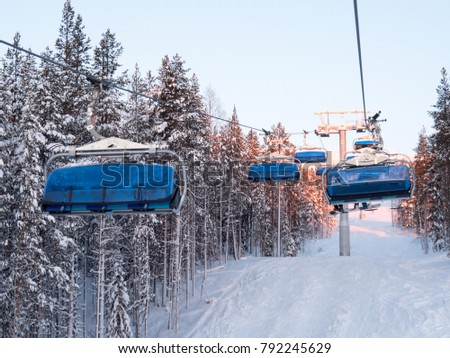 Ski lift with seats going over the mountain and paths from skies and snowboards. Ski resort, snow, extreme vacation, active holidays.