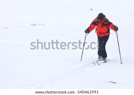 Ski mountaineer ascending a snow covered mountain in cloudy weather