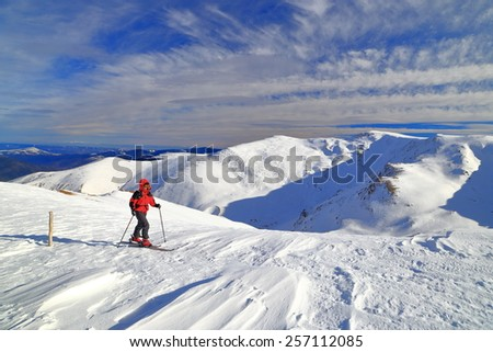Ski mountaineer ascending on alpine area in fine winter day - stock photo