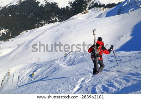 Ski mountaineer carries skies on the backpack in winter - stock photo