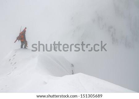 Ski mountaineer climbing a snowy ridge in bad weather - stock photo