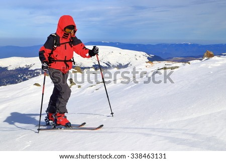 Ski mountaineer climbs on touring skis in sunny winter day - stock photo