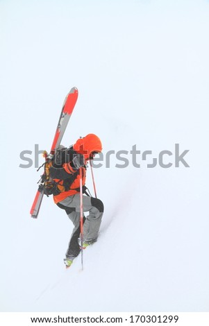 Ski mountaineer climbs snowy slope in bad weather