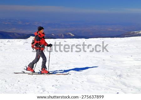 Ski mountaineer on flat terrain in sunny winter day - stock photo