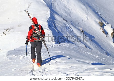 Ski mountaineer walking a steep snowy ridge with skis on the backpack - stock photo