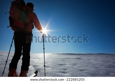 Ski mountaineer walks up hill on a glacier. Rear view, backlight, large copy space on the right. West Alps, Italy, Europe. - stock photo