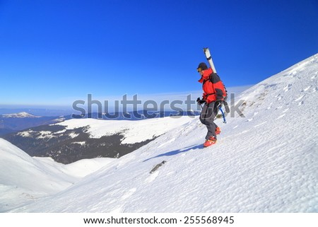 Ski mountaineer woman descending a steep ridge covered with snow